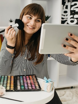 Blogger di trucco femminile smiley con streaming con tablet a casa
