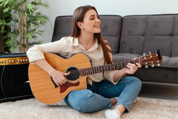 Смайлик женщина-музыкант играет на акустической гитаре