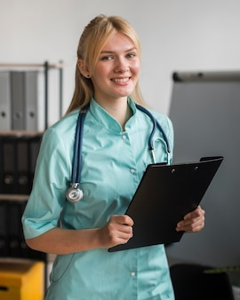 Smiley female nurse in the office with stethoscope and notepad