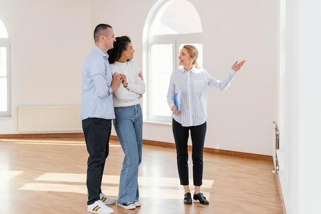 Agente immobiliare femminile di smiley che mostra casa vuota alla coppia