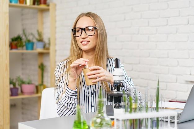 그녀의 책상에서 웃는 여성 연구원