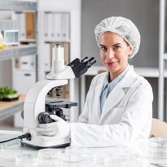 Smiley female researcher in the biotechnology laboratory with microscope