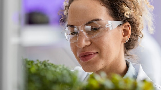 안전 안경 및 공장 실험실에서 웃는 여성 연구원