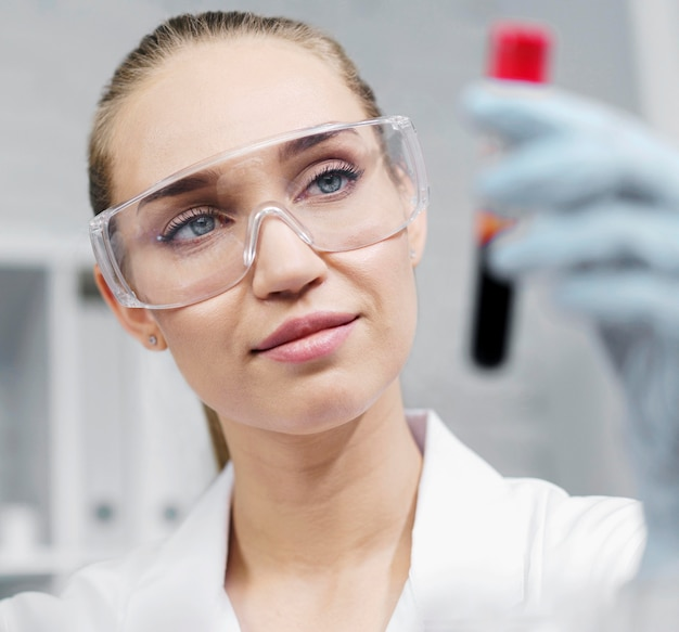 테스트 튜브와 안전 안경 실험실에서 웃는 여성 연구원