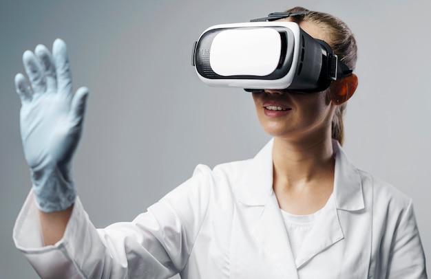 가상 현실 헤드셋을 사용하는 웃는 여성 연구원