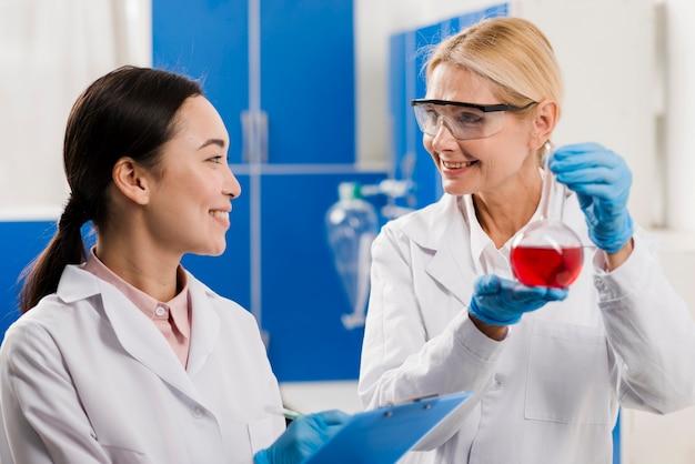 Scienziate femminili che tengono sostanza in laboratorio