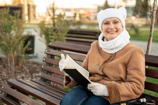 Улыбающаяся женщина сидит на скамейке и читает