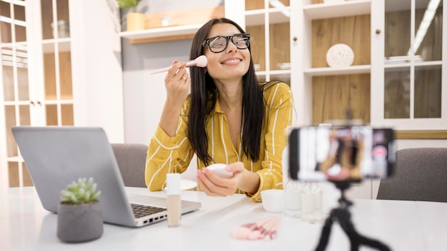 Smiley female vlogger at home with smartphone and brush