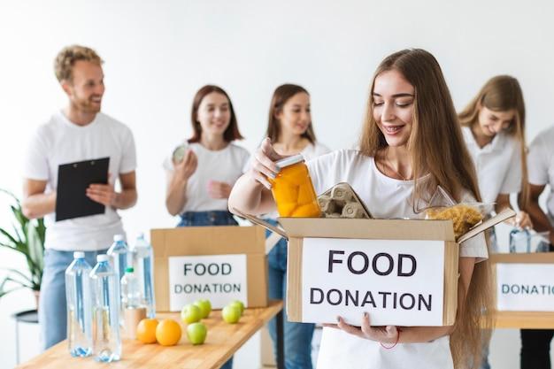 Volontario femminile di smiley e amici che tengono le donazioni di cibo
