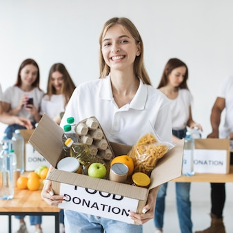 Смайлик-волонтер женщина держит коробку пожертвований на еду