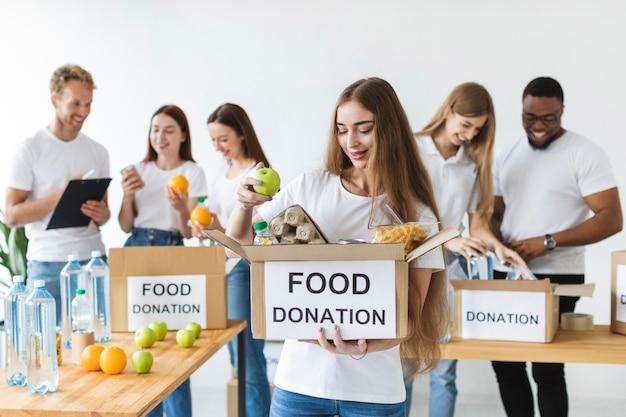 Смайлик-волонтер-женщина держит коробку с пожертвованиями