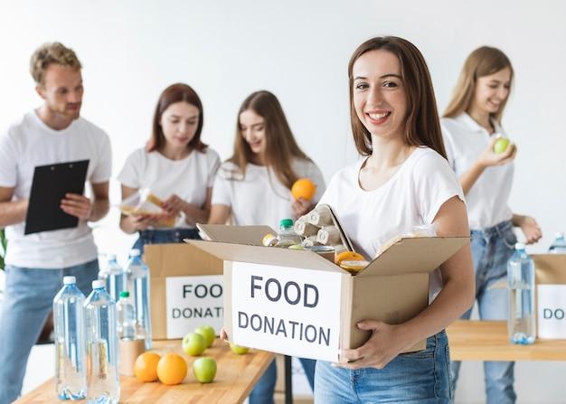 Смайлик-волонтер-женщина держит коробку с пожертвованиями на еду