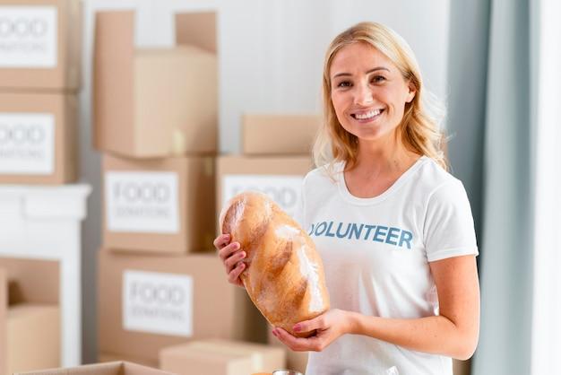 寄付のパンを持って笑顔の女性ボランティア
