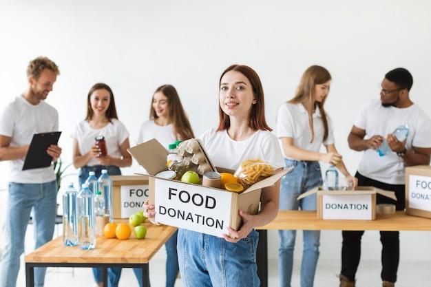 Volontario femminile di smiley che tiene casella di donazione con il cibo