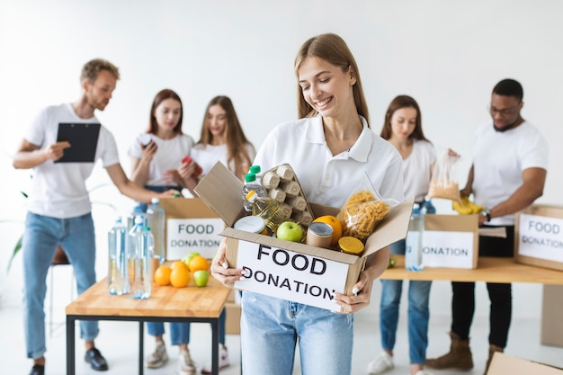Volontario femminile di smiley che tiene le donazioni di cibo nella casella