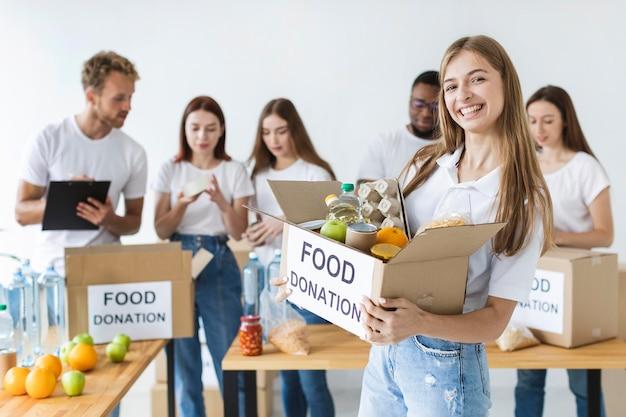 Смайлик-волонтер-женщина держит пожертвования на еду