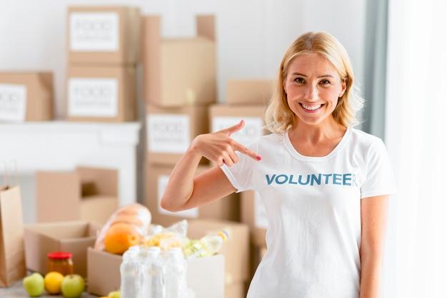 Улыбающаяся женщина-волонтер позирует, указывая на свою футболку