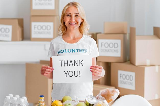 食べ物を寄付してくれてありがとうスマイリー女性ボランティア