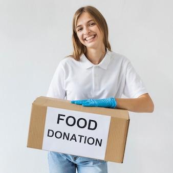 募金箱を保持している手袋を持つスマイリー女性ボランティア