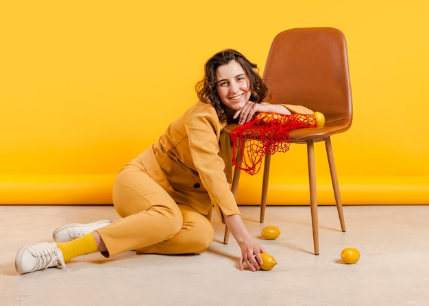 Smiley female with lemons on chair