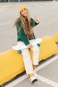 Smiley female with skateboard showing peace sign