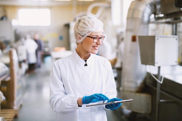 Смайлик работница в стерильной одежде с помощью планшета и проверки, как работает производственная линия.