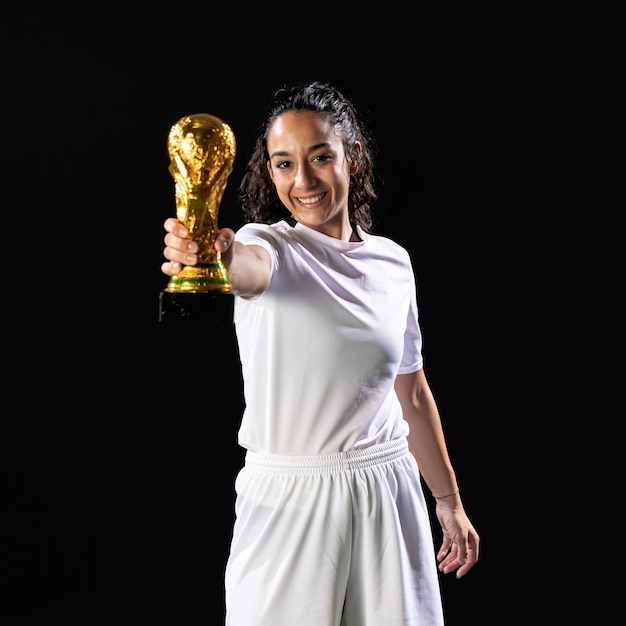 Smiley footballer holding world cup