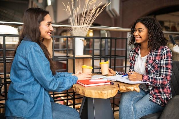 Улыбающиеся друзья вместе делают домашнее задание в кафе