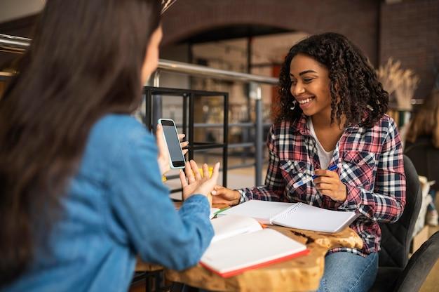 Улыбающиеся друзья делают домашнее задание с помощью смартфона в кафе