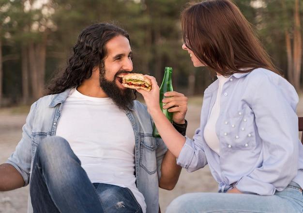 Amici di smiley che mangiano e bevono birra all'aperto