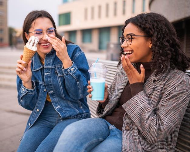 Друзья-смайлы веселятся вместе на свежем воздухе с мороженым и молочным коктейлем