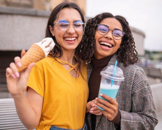 Улыбающиеся друзья веселятся вместе с молочными коктейлями