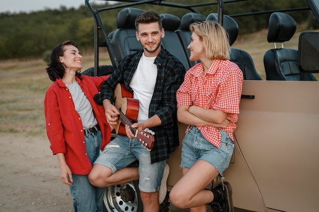 Smiley friends playing guitar while traveling by car