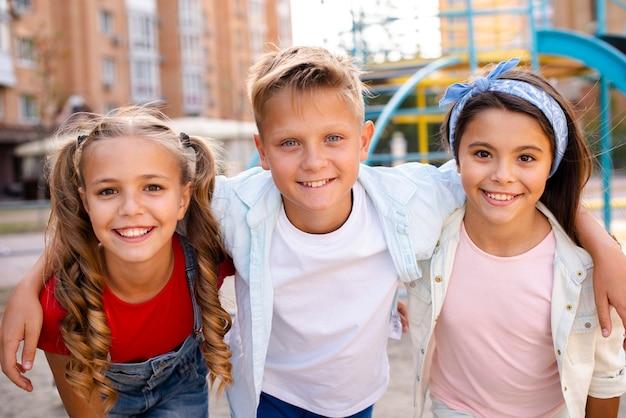 Улыбающиеся друзья позируют перед камерой на детской площадке