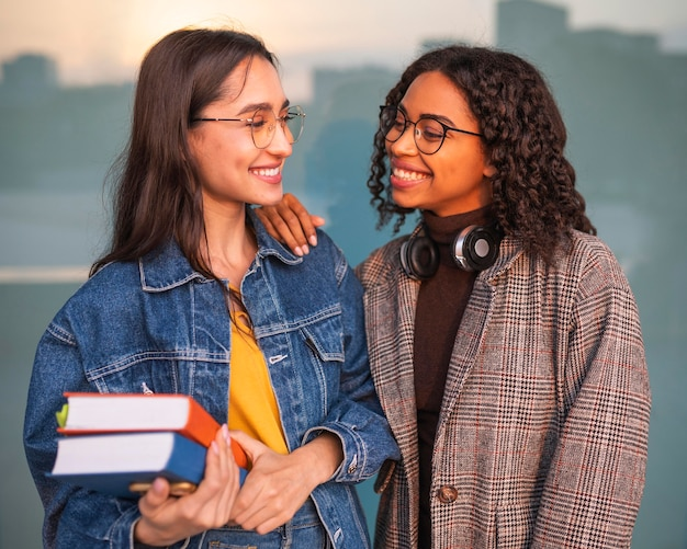 Smiley friends posing together with books and headphones