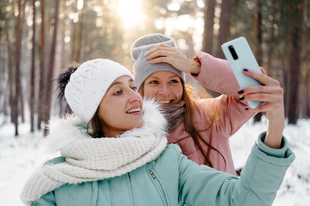Amici di smiley che prendono selfie all'aperto in inverno