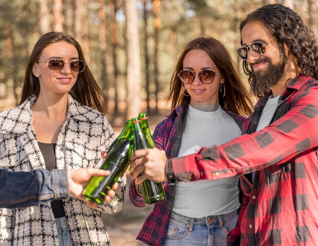 Smiley friends toasting with beer outdoors