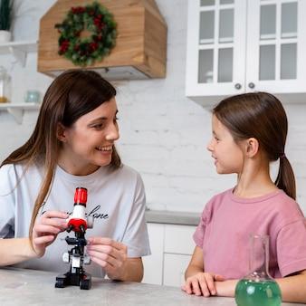 웃는 소녀와 어머니는 현미경으로 실험을하고