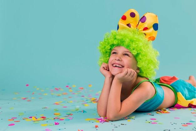 Smiley girl in clown costume with copy space
