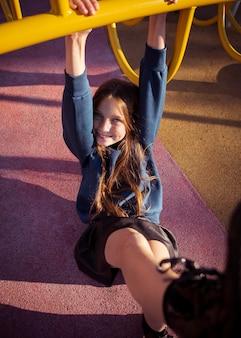 Смайлик девушка весело на детской площадке за пределами