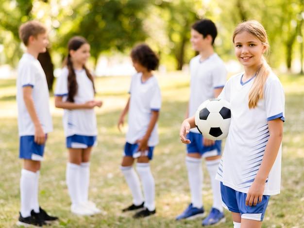 그녀의 팀 동료 옆에 축구를 들고 웃는 소녀