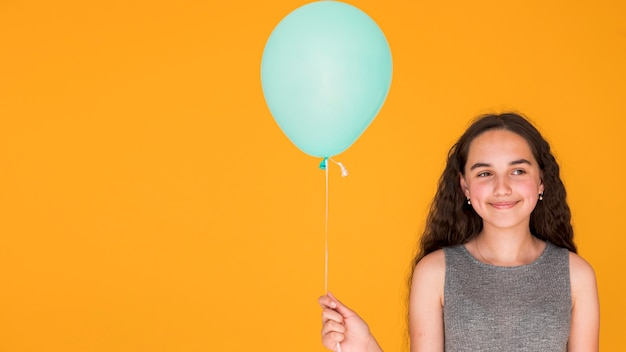 Smiley girl holding a blue balloon with copy space