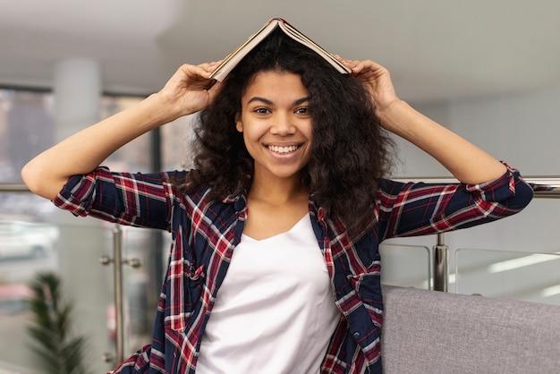 Улыбающаяся девушка держит книгу на голове