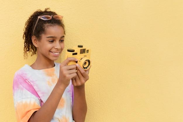 Ragazza sorridente che tiene in mano la fotocamera ripresa media