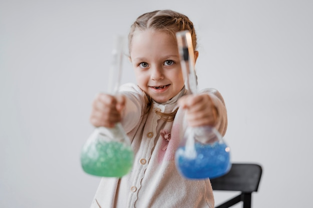 Smiley girl holding chemical elements in recipients