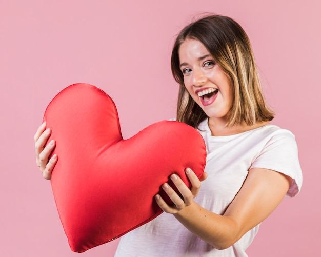 Smiley girl holding a heart shaped pillow