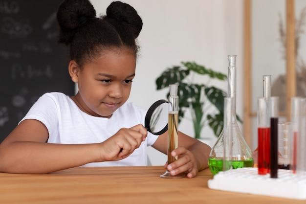 수업 시간에 화학에 대해 더 많이 배우는 웃는 소녀