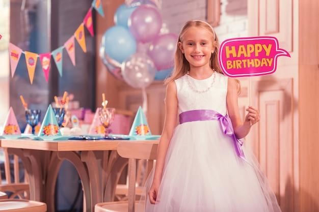 お誕生日おめでとうサインを持って探しているスマイリーガール