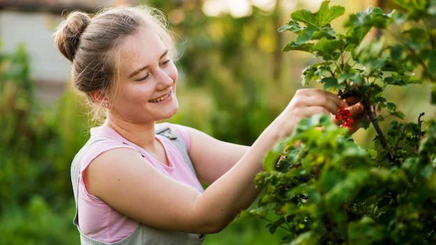 Smiley girl picking red berries