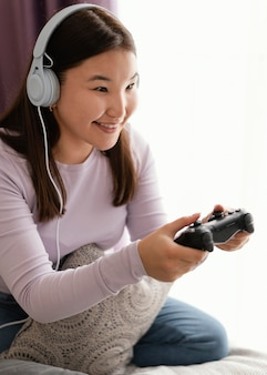 Smiley girl playing videogame in bed